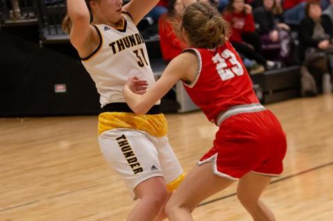 Mackenzie Muckey looks to pass the ball .